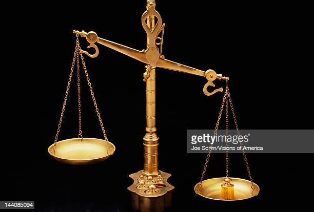 These are the golden Scales of Justice They represent the legal system and courts The scales here are shown unbalanced with the left side weighing...