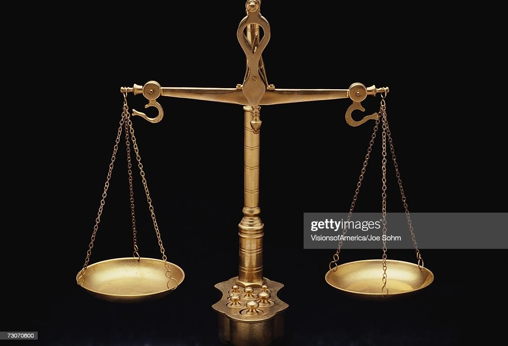 These are the golden scales of justice. They represent the legal systems and courts. These scales are shown in perfect balance against a black background. : Stock Photo