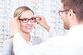 Optometrist putting a pair of glasses on a patient