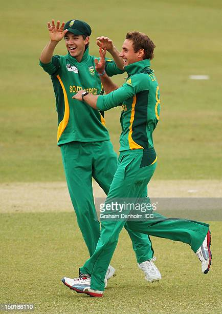 Theunis de Bruyn of South Africa celebrates with team mate Chad Bowes after taking the wicket of Naeem Islam jr of Bangladesh during the ICC U19...