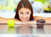 Pretty young woman trying to choose between unhealthy and healthy food options