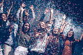 Group of beautiful young people throwing colorful confetti and looking happy