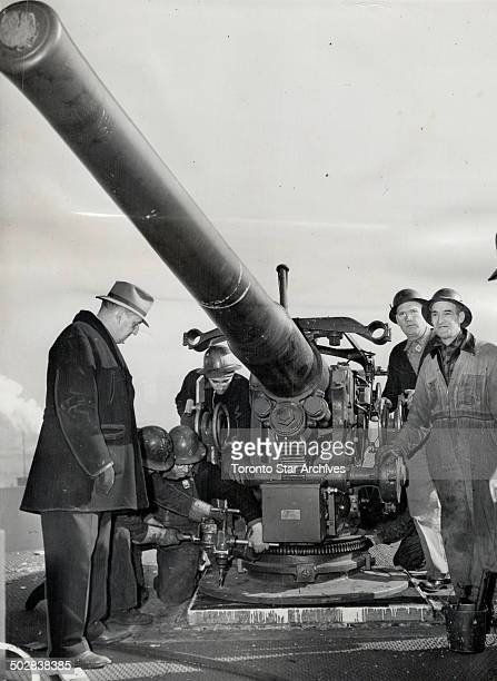 They're not popgunsand uncle sam's not fooling The long snout of a naval gun juts out from the deck of a merchant ship in Hoboken NJ as these workmen...