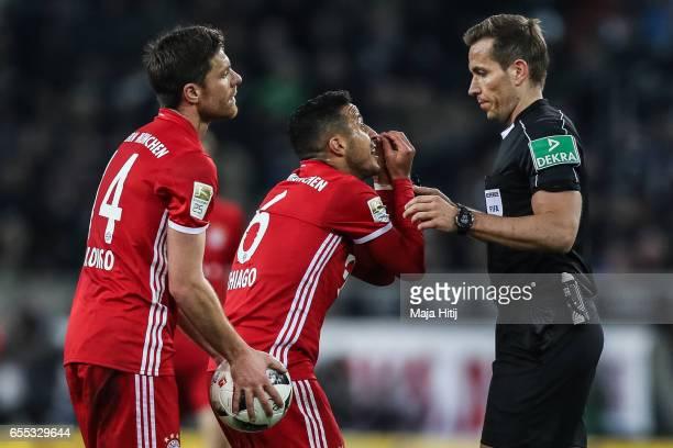 Thiago Alcantara do Nascimento of Bayern argues with a referee Tobias Stieler during the Bundesliga match between Borussia Moenchengladbach and...