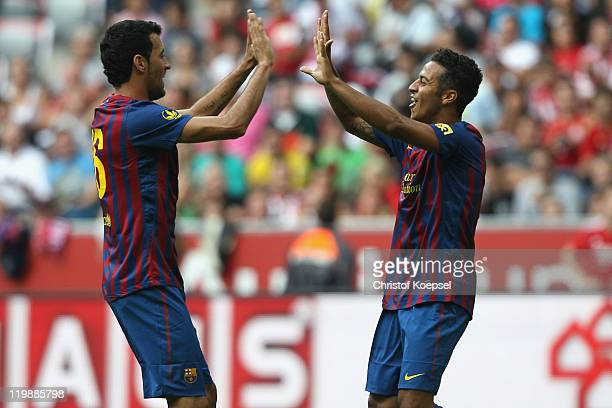 Thiago Alcantara of Barcelona celebrates the first goal with Sergio Busquets during the Audi Cup match between FC Barcelona and International de...