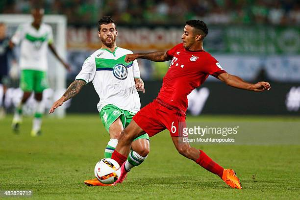 Thiago Alcantara of Bayern Muenchen battles for the ball with Vieirinha of VfL Wolfsburg during the DFL Supercup match between VfL Wolfsburg and FC...