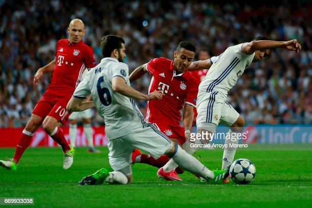 Thiago Alcantara of Bayern Muenchen competes for the ball with Nacho Fernandez of Real Madrid CF and his teammate Danilo Luiz da Silva during the...