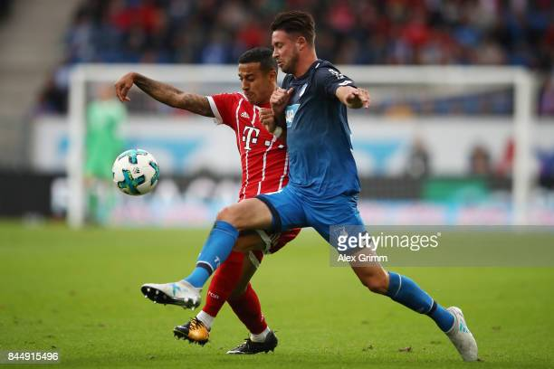 Thiago Alcantara of Bayern Muenchen fights for the ball with Mark Uth of Hoffenheim during the Bundesliga match between TSG 1899 Hoffenheim and FC...