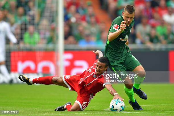 Thiago Alcantara of Bayern Muenchen fights for the ball with Maximilian Eggestein of Bremen during the Bundesliga match between SV Werder Bremen and...