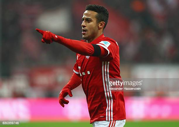 Thiago Alcantara of Bayern Muenchen runs to celebrate Xabi Alonso of Bayern Muenchen goal with him during the Bundesliga match between Bayern...