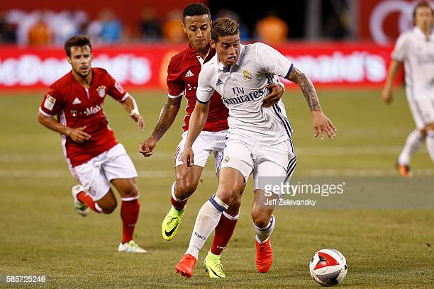 Thiago Alcantara of Bayern Munich grabs James Rodriguez of Real Madrid during their International Champions Cup match at MetLife Stadium on August 3...