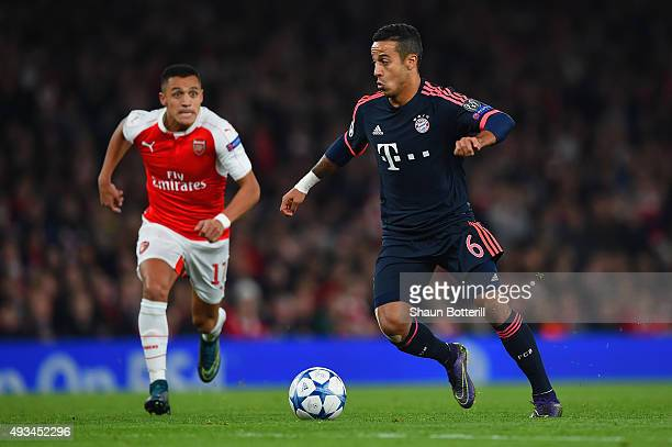 Thiago Alcantara of Bayern Munich is chased by Alexis Sanchez of Arsenal during the UEFA Champions League Group F match between Arsenal FC and FC...