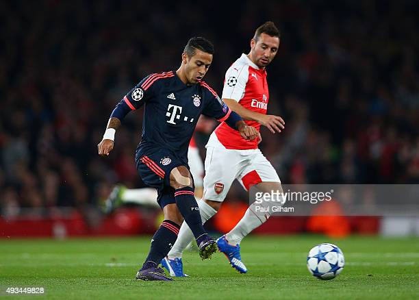 Thiago Alcantara of Bayern Munich is watched by Santi Cazorla of Arsenal during the UEFA Champions League Group F match between Arsenal FC and FC...
