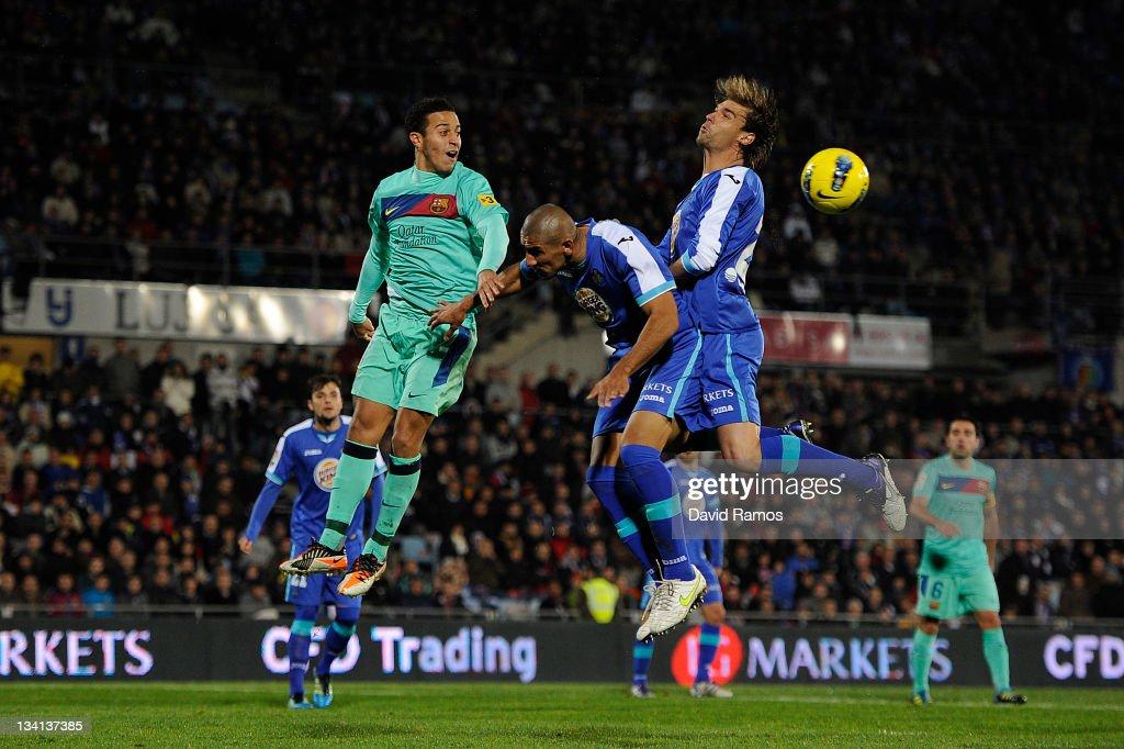 Thiago Alcantara of FC Barcelona duels for a high ball with Daniel Alberto Diaz and Juan Valera of Getafe CF during the La Liga match between Getafe...