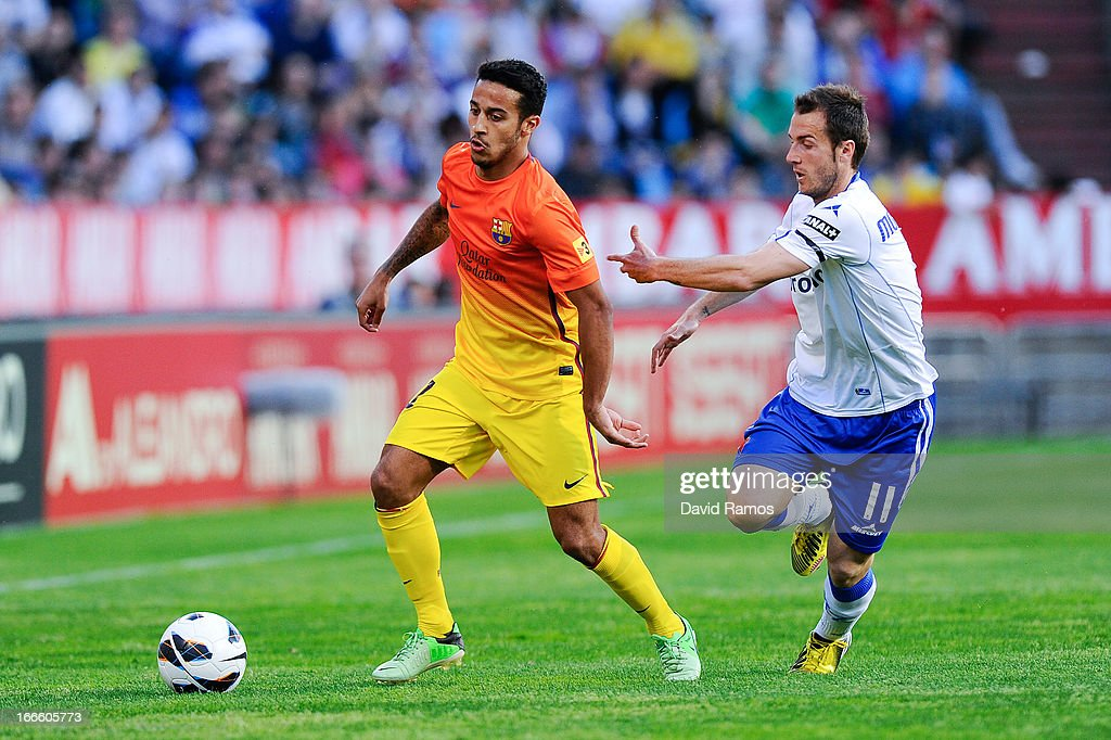 Thiago Alcantara of FC Barcelona duels for the ball with Paco Montanez of Real Zaragoza during the la Liga match between FC Barcelona and Real Zaragoza at La Romareda on April 14, 2013 in Zaragoza, Spain.
