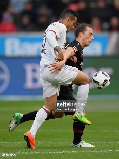 Thiago Alcantara of FC Bayern Muenchen and Julian Baumgartlinger of Leverkusen compete for the ball during the Bundesliga match between Bayer 04...