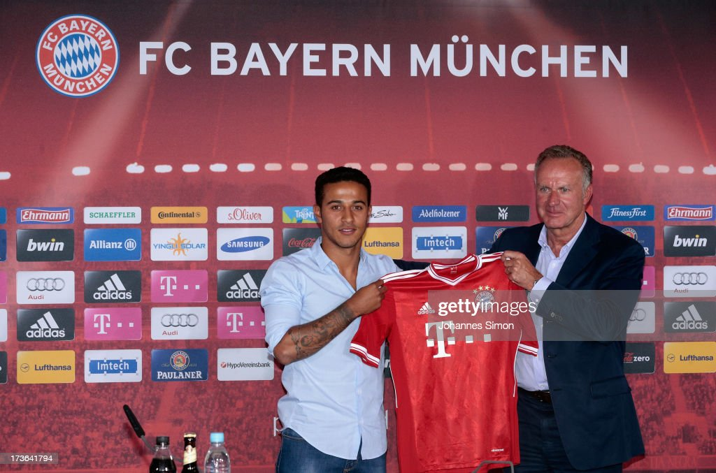 Thiago Alcantara (L) of FC Bayern Muenchen presents his new match jersey with FCB managing director <a gi-track='captionPersonalityLinkClicked' href=/galleries/search?phrase=Karl-Heinz+Rummenigge&family=editorial&specificpeople=634867 ng-click='$event.stopPropagation()'>Karl-Heinz Rummenigge</a> after a press conference at Bayern Muenchen's headquarters Saebener Strasse on July 16, 2013 in Munich, Germany.