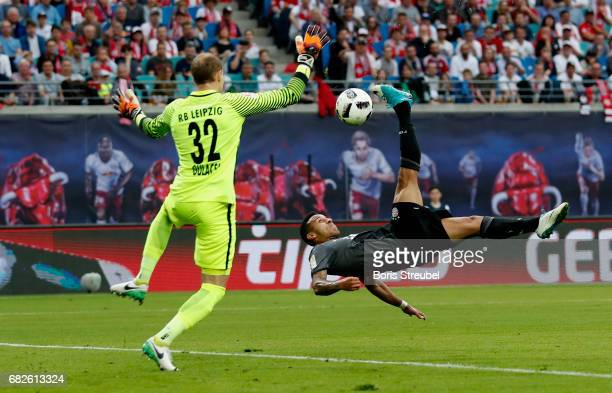 Thiago Alcantara of FC Bayern Muenchen takes an overhead kick against goalkeeper Peter Gulacsi of RB Leipzig during the Bundesliga match between RB...