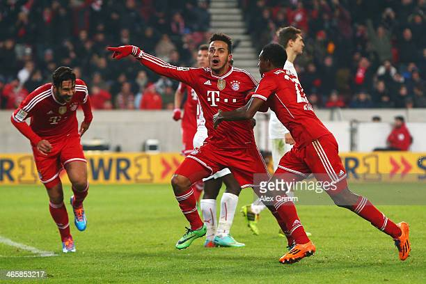 Thiago Alcantara of Muenchen celebrates his team's second goal with team mates David Alaba and Claudio Pizarro during the Bundesliga match between...