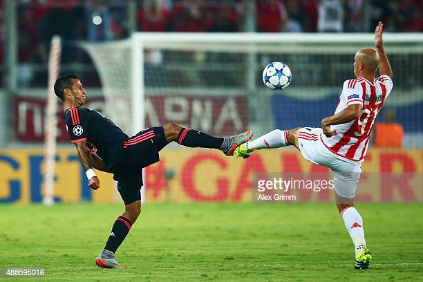 Thiago Alcantara of Muenchen is challenged by Esteban Cambiasso of Olympiacos during the UEFA Champions League Group F match between Olympiacos FC...