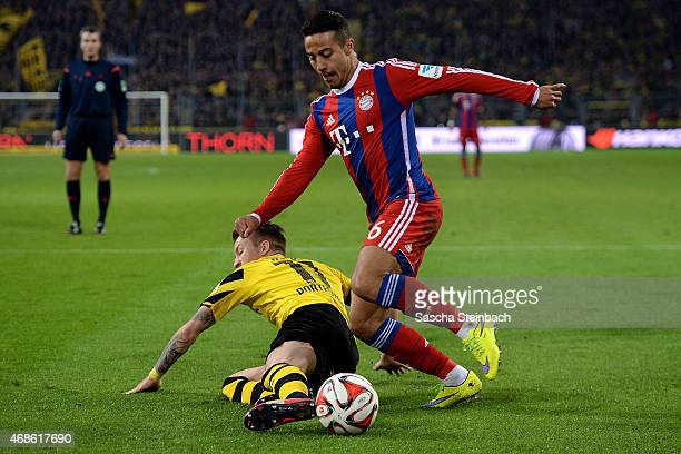 Thiago Alcantara of Muenchen is challenged by Marco Reus of Dortmund during the Bundesliga match between Borussia Dortmund and FC Bayern Muenchen at...
