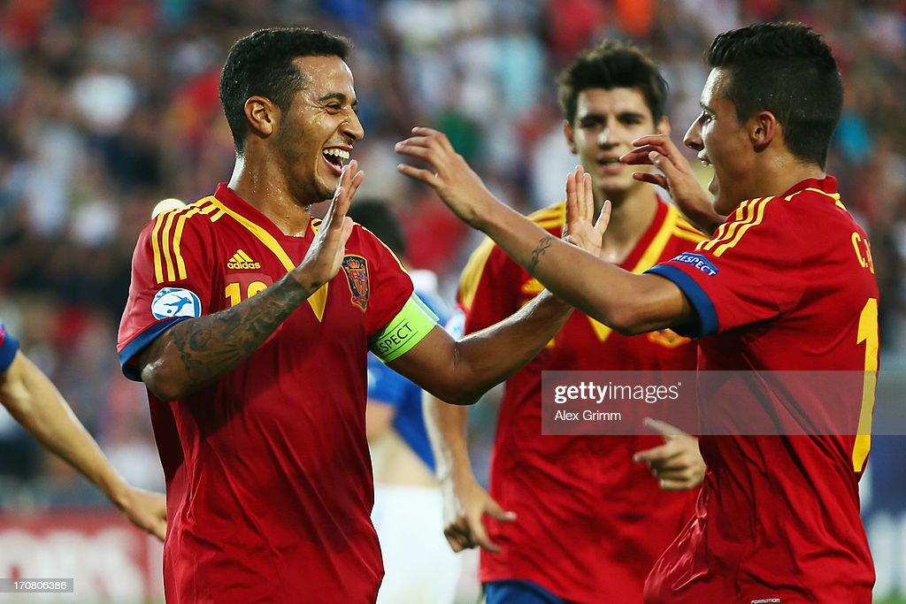 Thiago Alcantara of Spain celebrates his team's third goal with team mates <a gi-track='captionPersonalityLinkClicked' href=/galleries/search?phrase=Alvaro+Morata&family=editorial&specificpeople=6523866 ng-click='$event.stopPropagation()'>Alvaro Morata</a> and <a gi-track='captionPersonalityLinkClicked' href=/galleries/search?phrase=Cristian+Tello&family=editorial&specificpeople=8014696 ng-click='$event.stopPropagation()'>Cristian Tello</a> (L-R) during the UEFA European U21 Championship final match between Italy and Spain at Teddy Stadium on June 18, 2013 in Jerusalem, Israel.