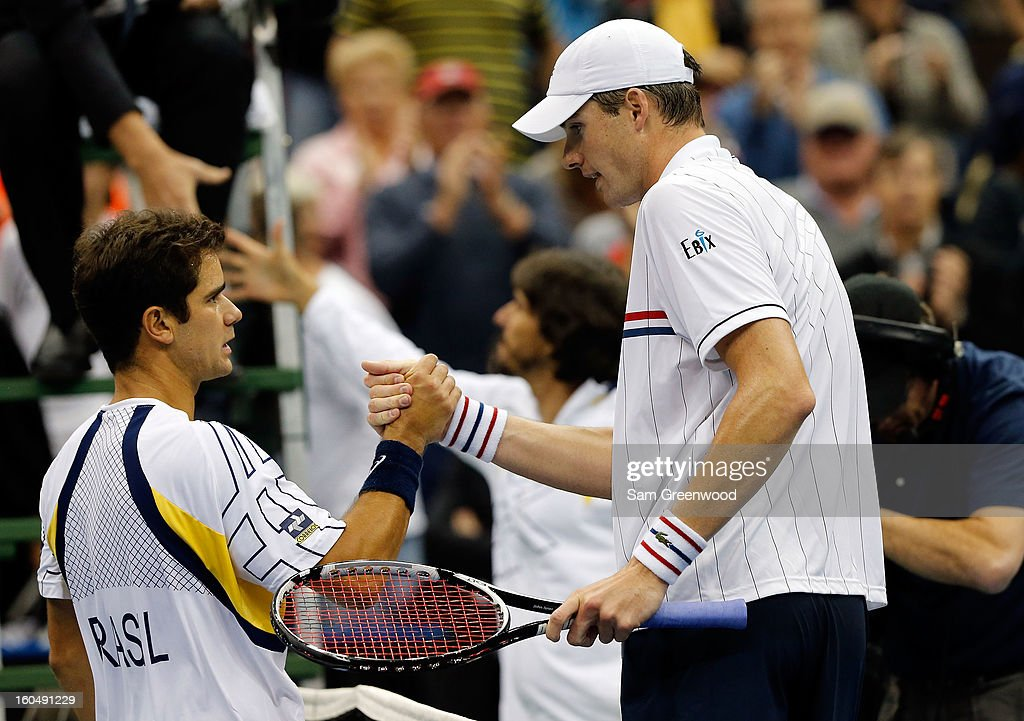 Thiago Alves of Brazil (L) shakes hands with John Isner of the United States following the Davis Cup first round match between the U.S. and Brazil at Veterans Memorial Arena on February 1, 2013 in Jacksonville, Florida. Isner won the game in three sets.