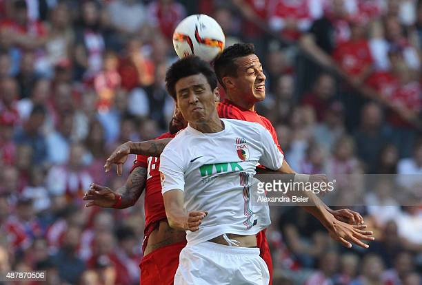Thiago and Arturo Vidal of Bayern Muenchen head for the ball with JaCheol Koo of FC Augsburg during the Bundesliga match between FC Bayern Muenchen...