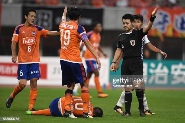 Thiago Galhardo of Albirex Niigata lies injured while his team mates protest to referee Koichiro Fukushima during the JLeague J1 match between...