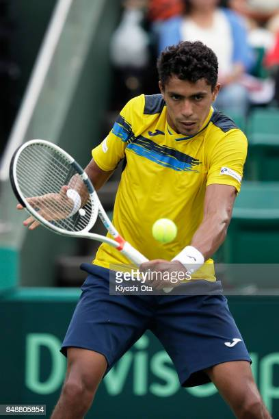 Thiago Monteiro of Brazil plays a backhand in his singles match against Yuichi Sugita of Japan during day four of the Davis Cup World Group Playoff...