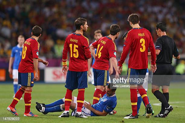 Thiago Motta of Italy is surrounded by Spain players as he lies on the turf injured during the UEFA EURO 2012 final match between Spain and Italy at...