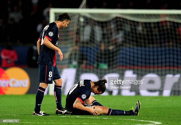 Thiago Motta of PSG checks on teammate Zlatan Ibrahimovic after he goes down injured during the UEFA Champions League quarter final first leg match...