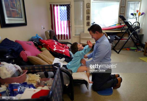 Thiago Nunez is dressed by his father Richard at their home in Stoneham MA on Mar 18 2017 Richard has taken care of his son since his wife Rosanna...