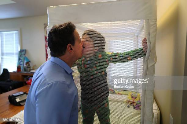 Thiago Nunez tries to kiss his father Richard from inside a special netted bed where he got up from a short rest while his father was doing laundry...