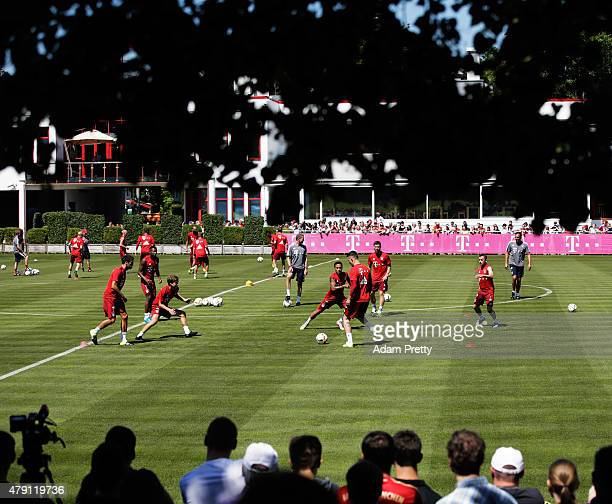 Thiago of FC Bayern and team mates are watched by fans during training at the FC Bayern Muenchen training grounds on July 1 2015 in Munich Germany
