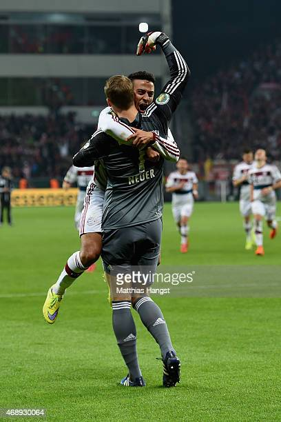 Thiago of FC Bayern Muenchen celebrates with team mate Manuel Neuer as he scores the final penalty during the DFB Cup Quarter Final match between...