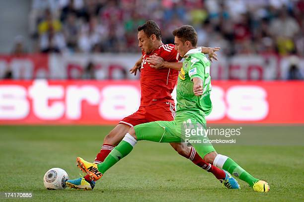 Thiago of FC Bayern Muenchen is challenged by Branimir Hrgota of Borussia Moenchengladbach during the Telekom 2013 Cup final between FC Bayern...