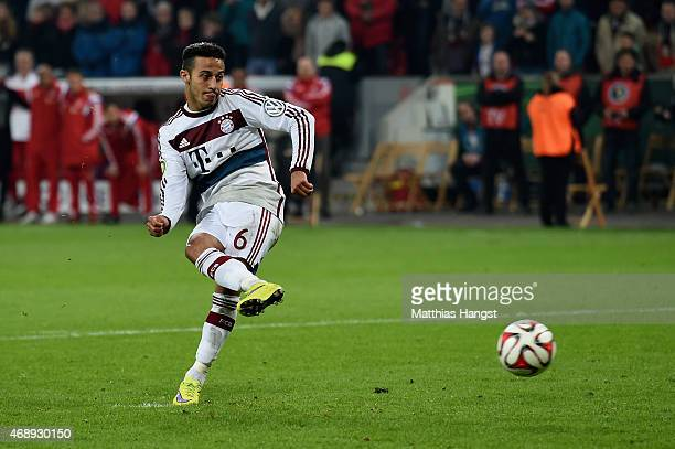 Thiago of FC Bayern Muenchen scores the final penalty during the DFB Cup Quarter Final match between Bayer Leverkusen and FC Bayern Muenchen at...