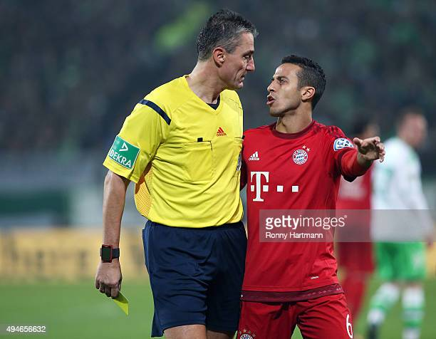 Thiago of Muenchen argues with referee Knut Kircher during the DFB Cup second round match between VfL Wolfsburg and FC Bayern Muenchen at Volkswagen...