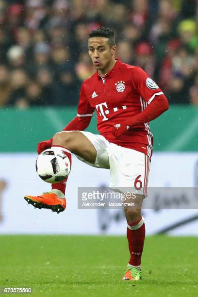 Thiago of Muenchen runs with the ball during the DFB Cup semi final match between FC Bayern Muenchen and Borussia Dortmund at Allianz Arena on April...
