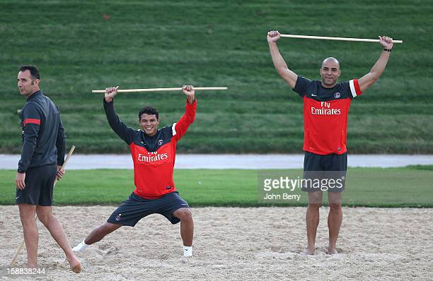 Thiago Silva and Alex Dias Da Costa of PSG warm up during a Paris Saint Germain training session at the Aspire Academy for Sports Excellence on...