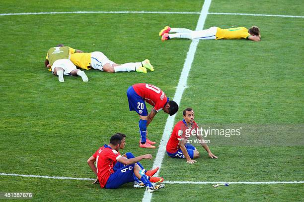 Thiago Silva and Neymar of Brazil celebrate as Mauricio Isla Charles Aranguiz and Marcelo Diaz of Chile look on after Brazil's win in a penalty...