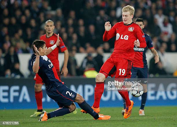 Thiago Silva of Paris SaintGermain tackles Julian Brandt of Bayer Leverkusen during the UEFA Champions League Round of 16 second leg match between...
