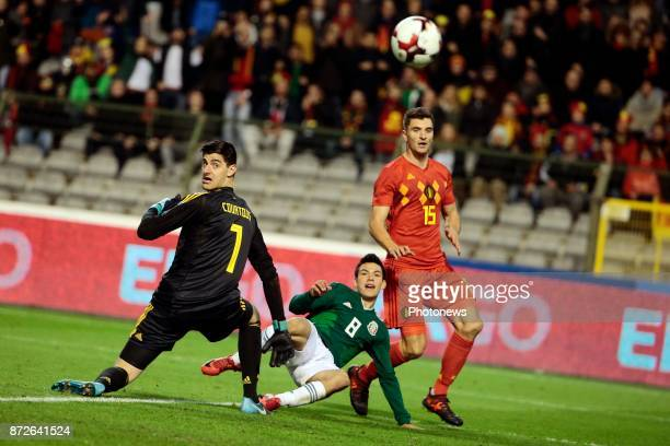 Thibaut Courtois goalkeeper of Belgium looks at the ball from Hirving Lozano forward of Mexico during a FIFA international friendly match between...