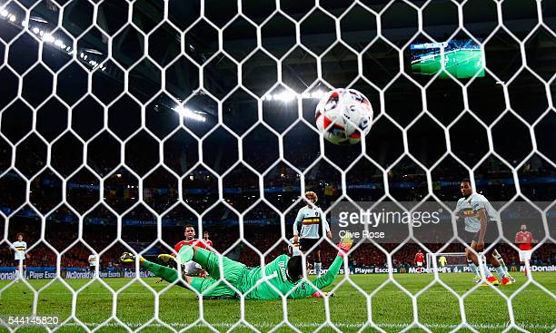 Thibaut Courtois of Belgium dives in vain as Hal RobsonKanu of Wales scores his team's second goal during the UEFA EURO 2016 quarter final match...