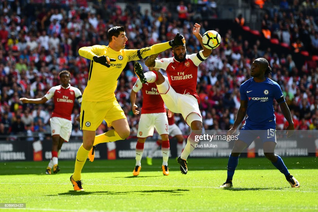 Thibaut Courtois of Chelsea and Alexandre Lacazette of Arsenal colide while both attempting to get to the ball during the The FA Community Shield final between Chelsea and Arsenal at Wembley Stadium on August 6, 2017 in London, England.