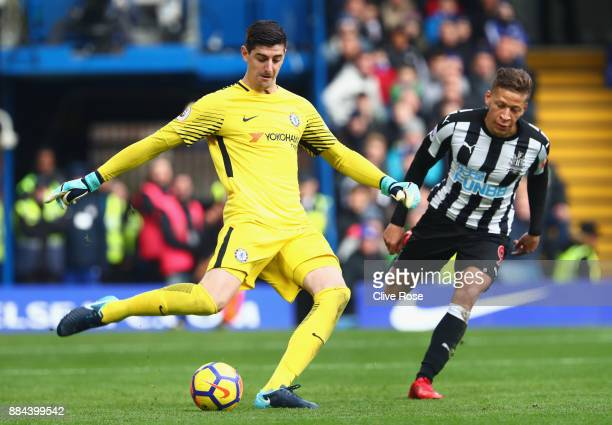 Thibaut Courtois of Chelsea clears the ball while under pressure from Dwight Gayle of Newcastle United during the Premier League match between...