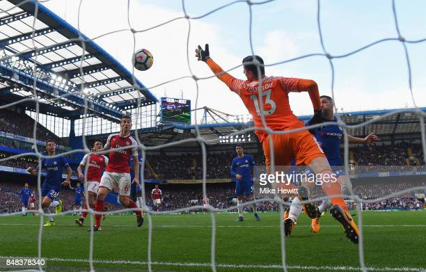 Thibaut Courtois of Chelsea dives as Shkodran Mustafi of Arsenal scores but it is later rulled for offside during the Premier League match between...