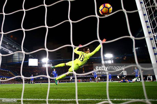 Thibaut Courtois of Chelsea dives in vain as Christian Eriksen of Tottenham Hotspur scores the opening goal during the Premier League match between...