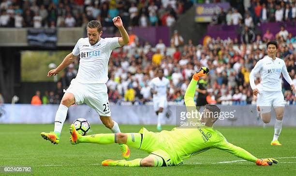 Thibaut Courtois of Chelsea fouls Gylfi Sigurdsson of Swansea City to concede a penalty kick during the Premier League match between Swansea City and...